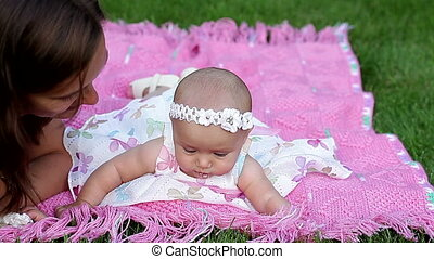 beautiful little baby girl with her mother lying on a pink...