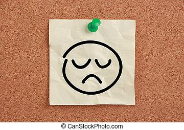 Sad Face Note - Sad face sticky note pinned on corkboard.