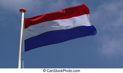 Dutch national flag in blue sky waving in wind -Kingdom of The Netherlands