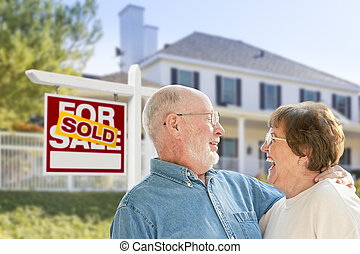 Senior Couple in Front of Sold Real Estate Sign, House -...
