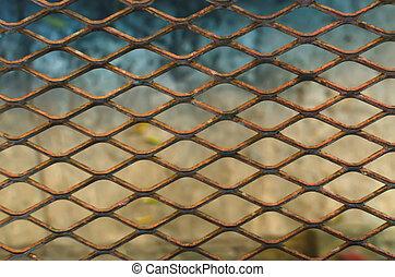 Rusted steel mesh behind street .