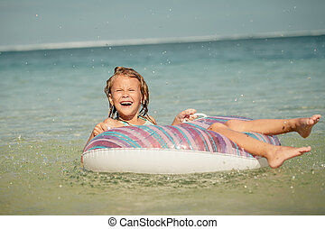 little girl lying on the inflatable rubber circle in the sea...