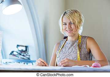 Atelier worker - Young blonde needlewoman at studio with...