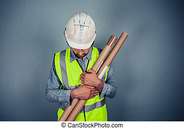 Engineer with building plans - An engineer is holding a...