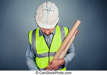 Young engineer with building plans - A young engineer in...