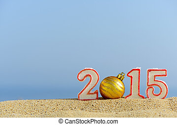 New year 2015 sign with christmas ball on a beach sand