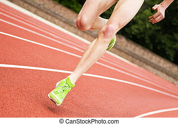 Oval running - Legs and shoes of a long distance runner on...