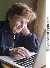 Old woman working on a laptop at his home.