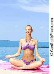 Serene young woman sitting meditating - Serene young woman...