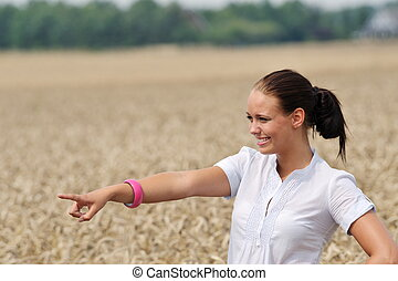 attractive young woman pointing at something