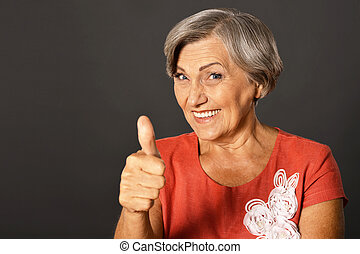 Portrait of elderly woman showing thumb up