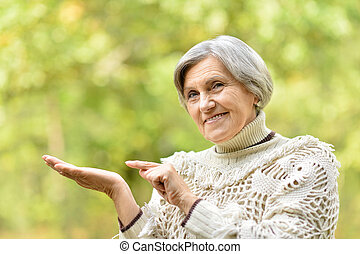 Senior woman pointing on her palm in the park in autumn
