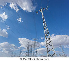 Wide view of electric tower group over blue sky and clouds -...