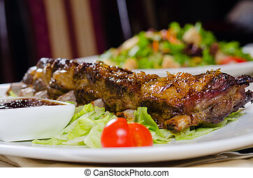 Rack of Grilled Pork Ribs on Plate in Restaurant - Close Up...