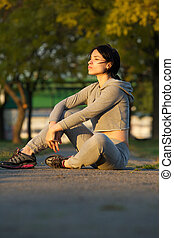 Young female athlete sitting outdoors