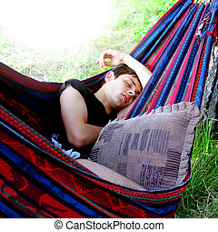 Teenager sleeping in the Hammock on the Nature