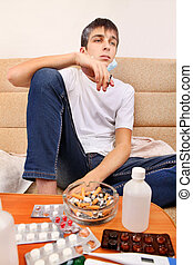 Sick Teenager smoking Cigarette on the Sofa with the Pills...