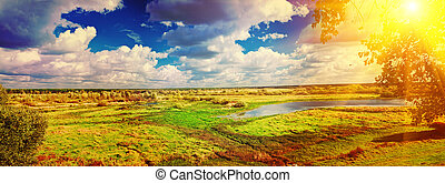 panoramic view on big meadow with small flood sky with sun insta
