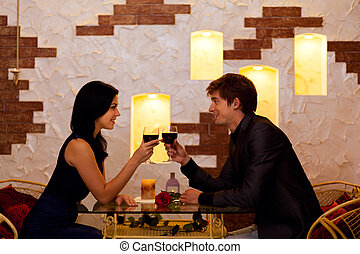 Young happy couple romantic date drink glass of red wine at...