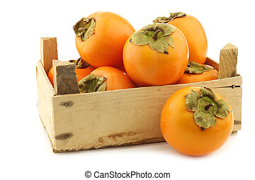 fresh kaki fruit in a wooden crate on a white background