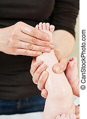 Masseur massaging a child leg