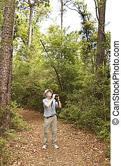 Man with Binoculars Birdwatching on a Forest Trail