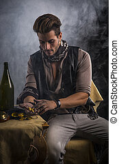 Young Man in Pirate Fashion Outfit Looking at Gold in Hand -...