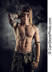 Shirtless male model wearing a bandanna smiling on smoky...