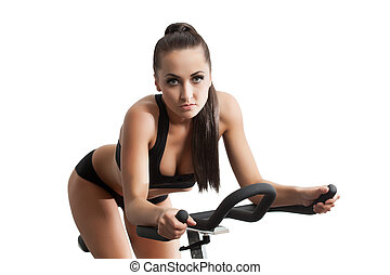 Sexy female athlete exercising on stationary bike - Image of...