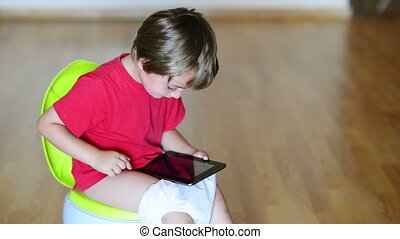 Tablet Dependence - Boy on potty using tablet pc