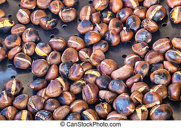 Grilling chestnuts. - Grilled chestnuts being selled at...