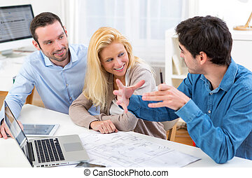 young serious couple meeting a real estate agent - View of a...