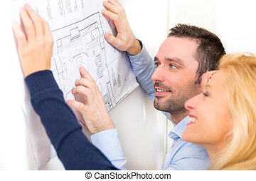 Young couple studying plans of their future house