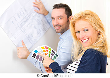 Young couple choosing colors of their future house