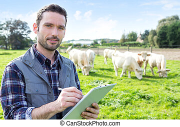 Young attractive farmer working in a field - View of a Young...