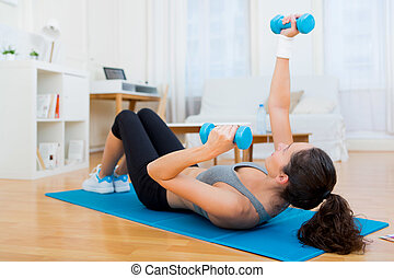 Young attractive girl doing exercise at home - view of a...