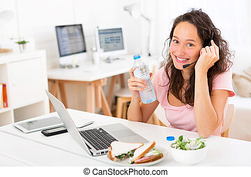 Young attractive student drinking water while working - View...