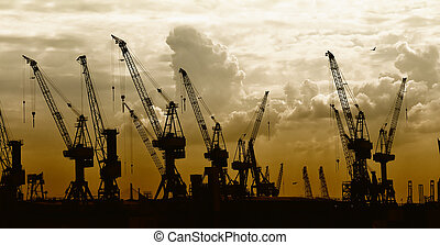 �construction silhouette of cranes on sunset background