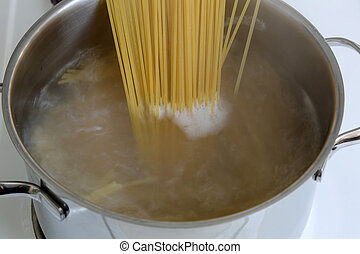 Preparing spaghetti pasta meal: cooking noodles in water in...