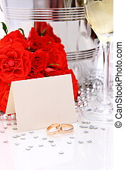 Two golden wedding rings with card, champagne glasses, red...