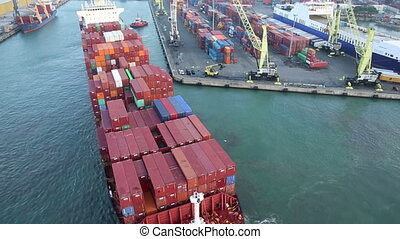 Aerial view of big cargo ship full of containers docking at...