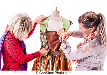 Seamstress working - two happy seamstresses working on a...