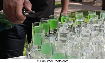 Barmen hand with bottle pouring beverage into glasses, on...
