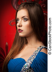 Gorgeous woman looking away dressed in blue dress on red...