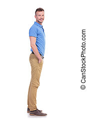 side of casual young man with hand in pocket