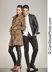 Fashion couple looking at the camera while holding their...