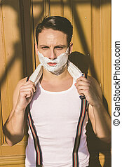 closeup of handsome man with shaving foam on his face and towel