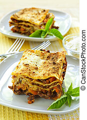 Plates of lasagna - Two servings of fresh baked lasagna on...