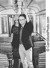 man with glasses in suit in a wagon train with a woman behind hi
