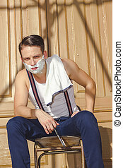 man with shaving foam on his face and towel around his neck siti